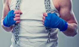 Handwrapped arms with chain. Boxer/kickboxer/muay thay fighter is handwrapped his arms and holding chain Royalty Free Stock Photos