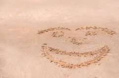 Handwrite face on the sand at the beach Royalty Free Stock Photos