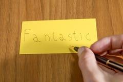 Handwrite fantastico su una carta gialla con una penna su una tavola immagini stock