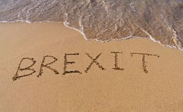 Handwrite text Brexit on sand coastline. And foam wave. On referendum, voted to exit United Kingdom from European Union - knows as Brexit, which is expected on stock photography