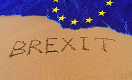 Handwrite text Brexit on sand coastline. And wave with EU flag pattern. On referendum, voted to exit United Kingdom from EU knows as Brexit, which is expected stock photos