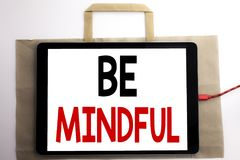 Handwriting Announcement text showing Be Mindful. Business concept for Mindfulness Healthy Spirit Written on shopping bag and tabl. Et white background, tablet Stock Photo