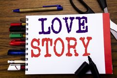 Handwriting Announcement text showing Love Story. Business concept for Loving Someone Heart  Written on notebook, wooden backgroun. D office equipment like pens Stock Photography