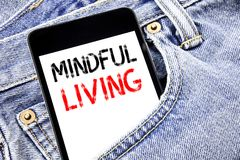 Handwriting Announcement text showing Mindful Living. Business concept for Life Happy Awareness Written phone mobile phone, cellph. One placed in man front jeans Stock Photo
