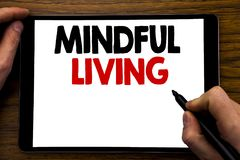 Handwriting Announcement text showing Mindful Living. Business concept for Life Happy Awareness Written on tablet laptop, wooden b. Handwriting Announcement text Royalty Free Stock Photography