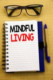 Handwriting Announcement text showing Mindful Living. Business concept for Life Happy Awareness Written on tablet laptop, wooden b. Handwriting Announcement text Stock Image
