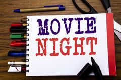Handwriting Announcement text showing Movie Night. Business concept for Wathing Movies Written on notebook, wooden background wit. Handwriting Announcement text royalty free stock photography