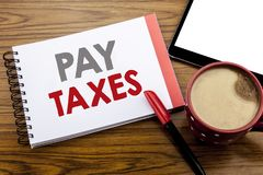 Handwriting Announcement text showing Pay Taxes. Business concept for Taxation Overtax Return Written on notepad note paper on woo. Handwriting Announcement text Stock Image
