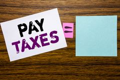 Handwriting Announcement text showing Pay Taxes. Business concept for Taxation Overtax Return written on sticky note paper on wood. Handwriting Announcement text Royalty Free Stock Photography
