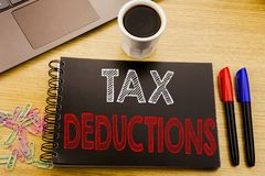 Handwriting Announcement text showing Tax Deductions. Business concept for Finance Incoming Tax Money Deduction written on noteboo. K book on wooden background Royalty Free Stock Photo