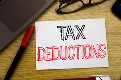Handwriting Announcement text showing Tax Deductions. Business concept for Finance Incoming Tax Money Deduction written on paper,. Wooden background in office Royalty Free Stock Image