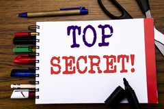 Handwriting Announcement text showing Top Secret. Business concept for Military Top Secret Written on notebook, wooden background. Office equipment like pens Stock Images