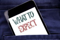 Handwriting Announcement text showing What To Expect. Business concept for Achieve Expectation Written phone mobile phone, cellpho. Ne placed in man front jeans Royalty Free Stock Photos