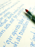 Handwriting & calligraphy pen on paper. An image showing a modern type of calligraphic manuscript pen, placed over a sample of calligraphy practise writing royalty free stock image