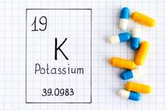 Handwriting chemical element Potassium K with pills. Close-up stock image