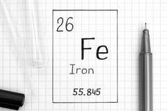 Handwriting chemicznego elementu żelaza Fe z czarnym piórem, próbną tubką i pipetą, obraz stock