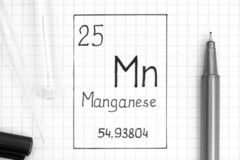 Handwriting chemicznego elementu manganu Mn z czarnym piórem, próbną tubką i pipetą, obraz royalty free