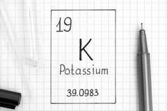 Handwriting chemicznego elementu potas K z czarnym piórem, próbną tubką i pipetą, zdjęcia stock