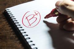 Handwriting Grade B Plus on Notebook Stock Image
