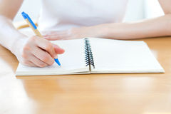 A handwriting, hand writes a pen in a notebook Stock Image