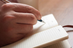 Handwriting, hand writes a pen in a notebook Stock Photography