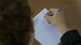 Handwriting, hand writes a pen on paper. Man writes a text on paper royalty free stock image