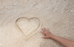 Handwriting of heart on golden sand with reach out of hand. View Royalty Free Stock Images