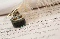 Handwriting,ink and quill pen. Handwriting poetry on old scroll, ink and quill pen in focus Stock Images