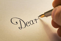 Handwriting letter with pen. Hand is writing calligraphic letter starting with dear using old pen on yellow paper Stock Photos