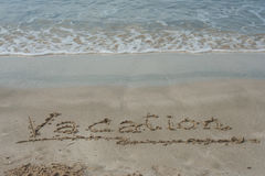 Handwriting message word `Vacation` on the beach. Royalty Free Stock Photos