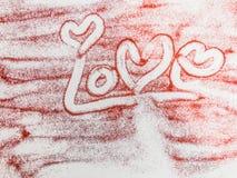 Handwriting miłość na czerwonej błyskotliwości Obrazy Royalty Free
