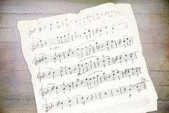 Handwriting music sheet. On a wooden background Royalty Free Stock Photography