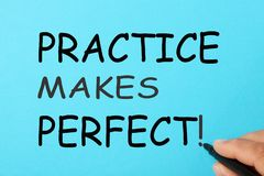 Practice Makes Perfect. Handwriting PRACTICE MAKES PERFECT on a blue background. Business Concept royalty free stock photography
