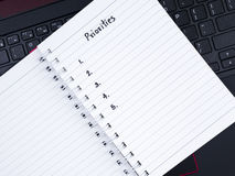 Handwriting Priorities on white notebook with laptop keyboard 1 Stock Photo
