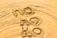 Handwriting Santa Claus`s Ho Ho Ho on the sand. stock image