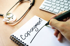 Handwriting sign copayment. Handwriting sign copayment in a note Royalty Free Stock Photos