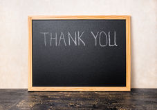 Handwriting tekst dziękuje ciebie napisze w chalkboard na craquelur Fotografia Stock