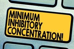 Handwriting teksta Minimalna Hamująca koncentracja Pojęcie znaczy niską koncentrację chemiczny Klawiaturowy klucz zdjęcia stock