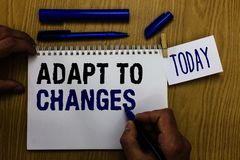 Handwriting text Adapt To Changes. Concept meaning Embrace new opportunities Growth Adaptation progress Man holding marker noteboo. K clothespin reminder wooden stock image