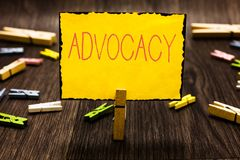 Handwriting text Advocacy. Concept meaning Profession of legal advocate Lawyer work Public recommendation Clothespin. Holding yellow paper note several royalty free stock image