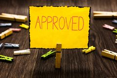 Handwriting text Approved. Concept meaning Approval Permission to do something Confirmation document Clothespin holding. Yellow paper note several clothespins royalty free stock image