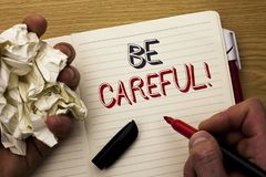 Handwriting text Be Careful. Concept meaning Caution Warning Attention Notice Care Beware Safety Security written by Man on Notebo. Handwriting text Be Careful Stock Photos