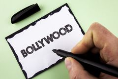 Handwriting text Bollywood. Concept meaning Indian cinema a source of entertainment written by Man on White sticky note paper hold. Handwriting text Bollywood royalty free stock photos