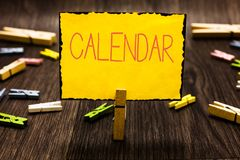 Handwriting text Calendar. Concept meaning Pages showing days weeks months of particular year Reminder Clothespin. Holding yellow paper note several clothespins stock images