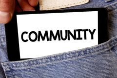 Handwriting text Community. Concept meaning Neighborhood Association State Affiliation Alliance Unity Group Man hold holding cell. Phone white screen message Stock Photos
