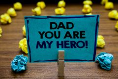 Handwriting text Dad You Are My Hero. Concept meaning Admiration for your father love feelings compliment Blurry wooden. Deck yellow and blue lob on ground royalty free stock image