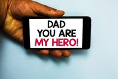 Handwriting text Dad You Are My Hero. Concept meaning Admiration for your father love feelings compliment Human hand. Hold mobile phone with some black and red royalty free stock photography