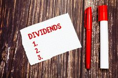 Handwriting text Dividends. Concept meaning sum of money paid regularly by company to shareholders out profits Blank. Torn Index sized Graph Paper Two Pens for stock images
