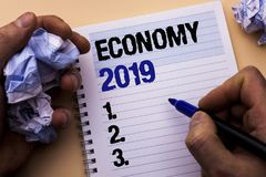 Handwriting text Economy 2019. Concept meaning Financial Currency Growth Market Earnings Trade Money written by Man on Notebook Bo. Handwriting text Economy 2019 Stock Images