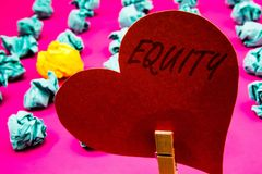 Handwriting text Equity. Concept meaning Value of a company divided into equal parts owned by shareholders Clothespin holding red. Heart paper crumpled papers royalty free stock photo